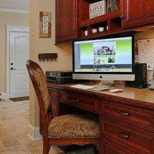 Immagine di un piccolo ufficio american style con pareti beige, pavimento in travertino, nessun camino e scrivania incassata