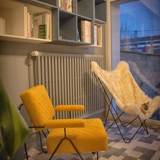 パリの中サイズのコンテンポラリースタイルのおしゃれなホームオフィス・仕事部屋 (ライブラリー、グレーの壁、ラミネートの床、暖炉なし、自立型机、マルチカラーの床) の写真