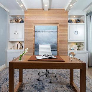 Großes Maritimes Arbeitszimmer mit Arbeitsplatz, blauer Wandfarbe, Travertin, freistehendem Schreibtisch, beigem Boden, freigelegten Dachbalken und Holzwänden in Miami
