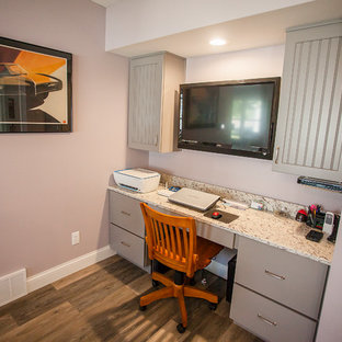 This is an example of a small rural home office and library in Cedar Rapids with purple walls, vinyl flooring, a built-in desk and grey floors.
