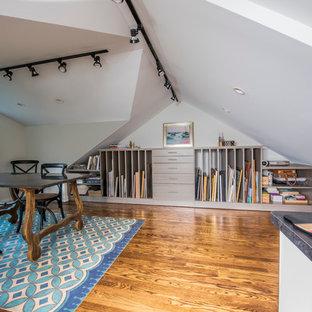 Mittelgroßes Stilmix Arbeitszimmer ohne Kamin mit Studio, weißer Wandfarbe, braunem Holzboden und freistehendem Schreibtisch in Chicago