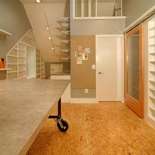 Imagen de sala de manualidades industrial, sin chimenea, con paredes grises, suelo de contrachapado y escritorio independiente