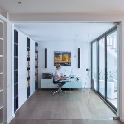 Study room - large contemporary freestanding desk medium tone wood floor and beige floor study room idea in London with white walls