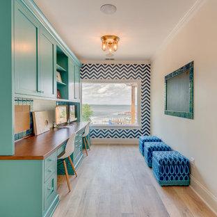 Ejemplo de despacho clásico renovado, de tamaño medio, con paredes multicolor, suelo de madera clara y escritorio empotrado