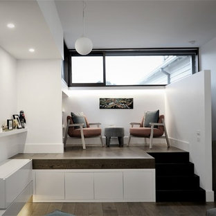 Design ideas for a medium sized contemporary home office and library in Melbourne with a reading nook, white walls, medium hardwood flooring, a ribbon fireplace and a concrete fireplace surround.
