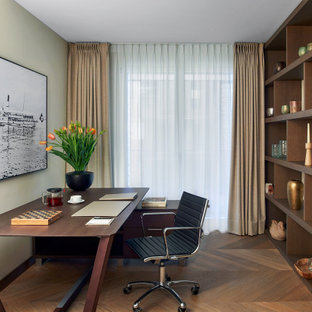 This is an example of a contemporary study in London with medium hardwood flooring, no fireplace and a freestanding desk.