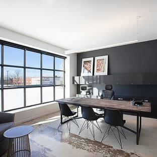 Immagine di un grande studio moderno con pareti nere, pavimento in cemento e scrivania autoportante