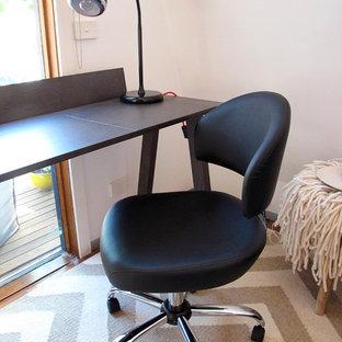 Foto di un piccolo atelier contemporaneo con pareti bianche, parquet chiaro, camino classico, cornice del camino in metallo, scrivania autoportante e pavimento arancione