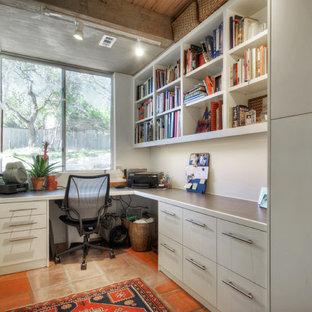 На фото: маленькое рабочее место в современном стиле с белыми стенами, встроенным рабочим столом и полом из терракотовой плитки без камина