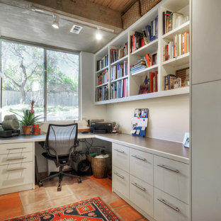 Ejemplo de despacho actual, pequeño, sin chimenea, con paredes blancas, escritorio empotrado y suelo de baldosas de terracota