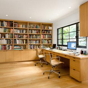 Foto på ett mellanstort retro hemmabibliotek, med vita väggar, ljust trägolv, ett inbyggt skrivbord och gult golv