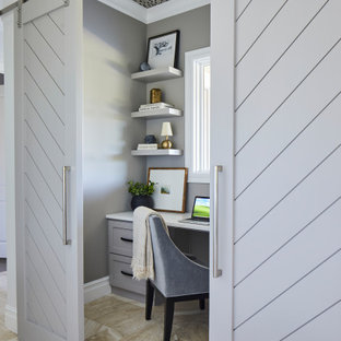 На фото: маленькое рабочее место в стиле неоклассика (современная классика) с серыми стенами, полом из травертина, встроенным рабочим столом, бежевым полом и потолком с обоями