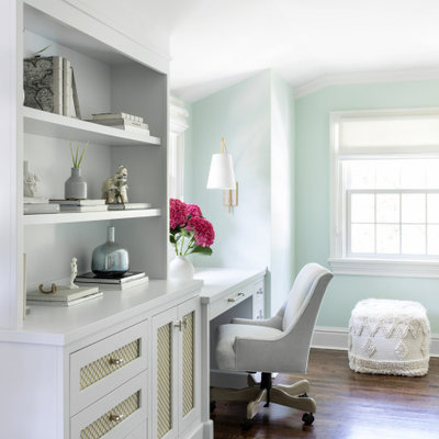 Mid-sized transitional built-in desk brown floor and medium tone wood floor study room photo in New York with green walls
