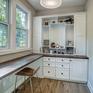 Inredning av ett modernt mellanstort hobbyrum, med beige väggar, linoleumgolv, ett inbyggt skrivbord och beiget golv