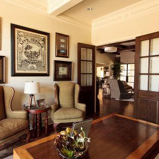 Bild på ett vintage hemmabibliotek, med vita väggar, mörkt trägolv, ett fristående skrivbord och brunt golv