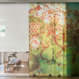 ニューヨークの中サイズのモダンスタイルのおしゃれな書斎 (白い壁、淡色無垢フローリング、自立型机) の写真
