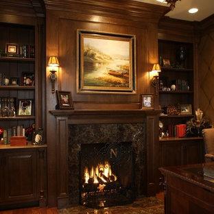 Idéer för ett stort amerikanskt hemmabibliotek, med mellanmörkt trägolv, en standard öppen spis, ett fristående skrivbord, bruna väggar och en spiselkrans i sten