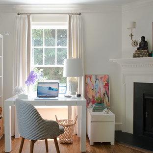 Imagen de despacho ecléctico, pequeño, con paredes blancas, suelo de madera en tonos medios, chimenea de esquina, marco de chimenea de piedra, escritorio independiente y suelo marrón
