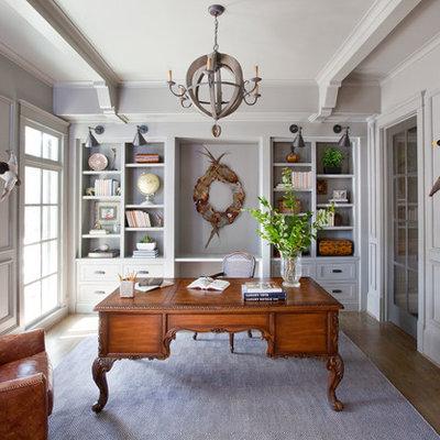 Example of a classic freestanding desk medium tone wood floor study room design in Atlanta with gray walls
