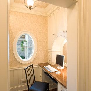 Diseño de despacho tradicional con paredes beige, suelo de madera oscura y escritorio empotrado