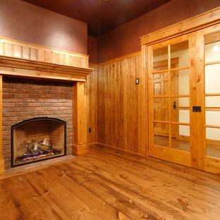 Esempio di un ufficio country di medie dimensioni con pavimento in legno massello medio, camino classico, cornice del camino in mattoni, pareti marroni e pavimento marrone
