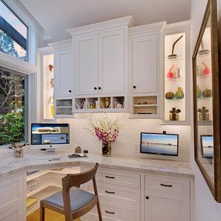 Cette image montre un bureau craftsman de taille moyenne avec un mur blanc, un sol en bois clair, aucune cheminée, un bureau intégré et un sol beige.