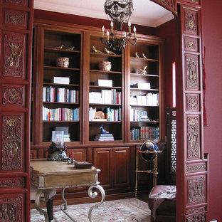 Mid-sized asian freestanding desk medium tone wood floor home office library photo in Orlando with red walls