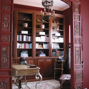 Idéer för mellanstora orientaliska arbetsrum, med ett bibliotek, röda väggar, mellanmörkt trägolv och ett fristående skrivbord