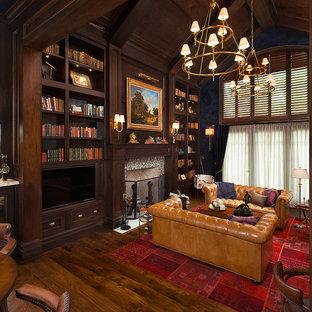 Immagine di un ampio studio classico con pareti blu, pavimento in legno massello medio, camino classico, cornice del camino piastrellata, scrivania incassata, libreria e pavimento marrone