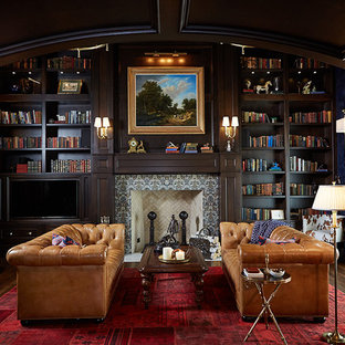 Modelo de despacho tradicional, extra grande, con paredes marrones, chimenea tradicional, marco de chimenea de baldosas y/o azulejos, escritorio empotrado, suelo marrón y suelo de madera en tonos medios