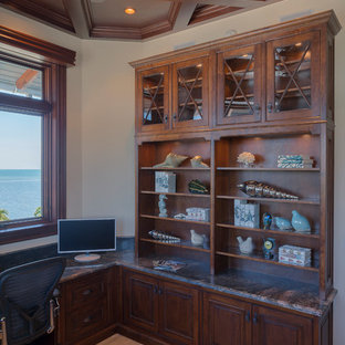 マイアミの大きいビーチスタイルのおしゃれな書斎 (ベージュの壁、トラバーチンの床、造り付け机、ベージュの床) の写真