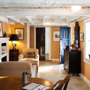 Immagine di un piccolo ufficio country con pareti beige, pavimento in gres porcellanato, camino classico, scrivania autoportante e cornice del camino in mattoni