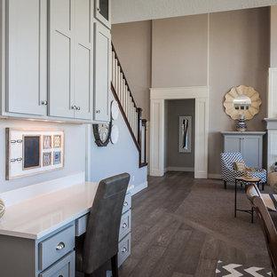 Cette photo montre un bureau craftsman de taille moyenne avec un mur gris, un sol en bois foncé, un bureau intégré, une cheminée standard et un manteau de cheminée en carrelage.