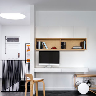 Scandinavian home office in Sydney with white walls, a built-in desk and black floor.