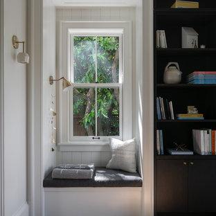 Ispirazione per un grande studio design con pareti bianche, pavimento in legno massello medio, pavimento marrone, libreria, nessun camino e scrivania autoportante