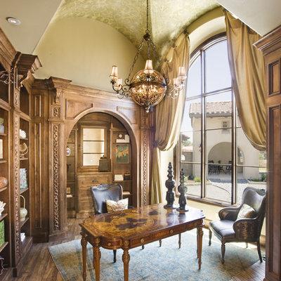 Example of a tuscan freestanding desk dark wood floor home office design in Austin with beige walls