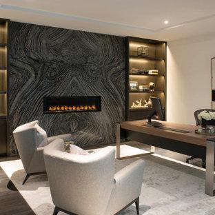Inspiration för mellanstora moderna hemmabibliotek, med vita väggar, mellanmörkt trägolv, en bred öppen spis, en spiselkrans i sten, ett fristående skrivbord och brunt golv