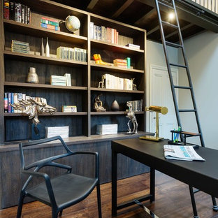 This is an example of a classic study in London with dark hardwood flooring, a freestanding desk and brown floors.
