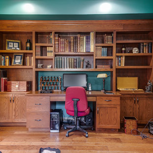Inspiration for a rustic built-in desk medium tone wood floor and brown floor home office remodel in DC Metro with blue walls