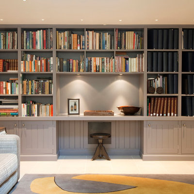 Example of a small classic built-in desk home office library design in London with white walls