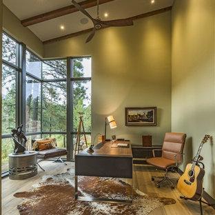 Modelo de despacho rústico con paredes verdes, suelo de madera clara, escritorio independiente y suelo beige