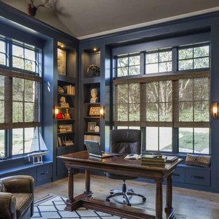 Inredning av ett klassiskt stort hemmabibliotek, med blå väggar, ett fristående skrivbord, brunt golv och ljust trägolv