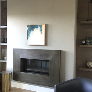 This is an example of a medium sized rustic home office and library in Salt Lake City with white walls, light hardwood flooring, a standard fireplace, a metal fireplace surround and a freestanding desk.