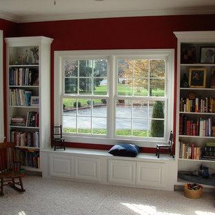 Klassisk inredning av ett mellanstort hemmabibliotek, med röda väggar, heltäckningsmatta och ett inbyggt skrivbord