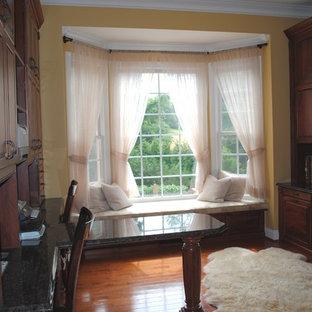 Idee per un grande ufficio tradizionale con pareti gialle e pavimento in legno massello medio