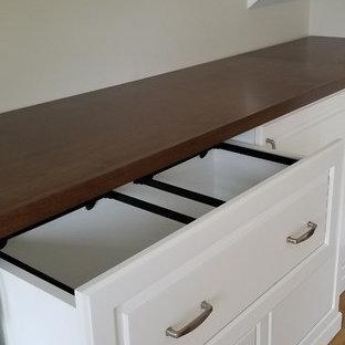 Cette photo montre un grand bureau chic avec un sol en bois brun, un bureau intégré et un sol orange.