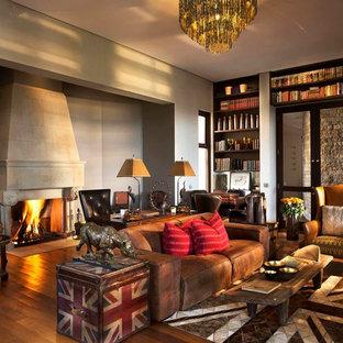 他の地域の大きいエクレクティックスタイルのおしゃれなホームオフィス・書斎 (無垢フローリング、標準型暖炉、石材の暖炉まわり、茶色い床、グレーの壁) の写真