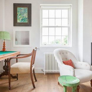 ロンドンの中サイズのモダンスタイルのおしゃれなホームオフィス・仕事部屋 (白い壁、淡色無垢フローリング、標準型暖炉、自立型机、ベージュの床) の写真
