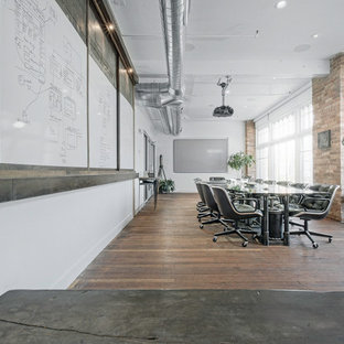 Inspiration for a large industrial study room in Salt Lake City with white walls, dark hardwood floors, no fireplace and a freestanding desk.