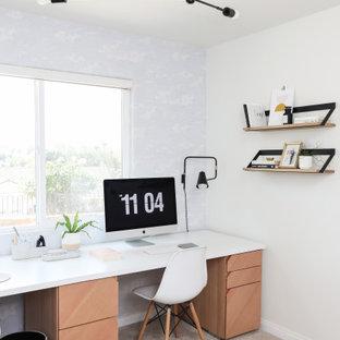 Стильный дизайн: маленькое рабочее место в современном стиле с белыми стенами, ковровым покрытием, встроенным рабочим столом, бежевым полом и обоями на стенах без камина - последний тренд